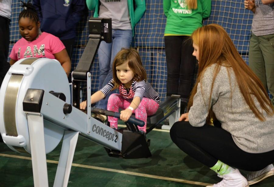 Freshman+rower+Amelia+Kanonczyk+guides+a+young+girl+using+a+rowing+machine.+The+event+offered+activities+in+more+than+10+sports.