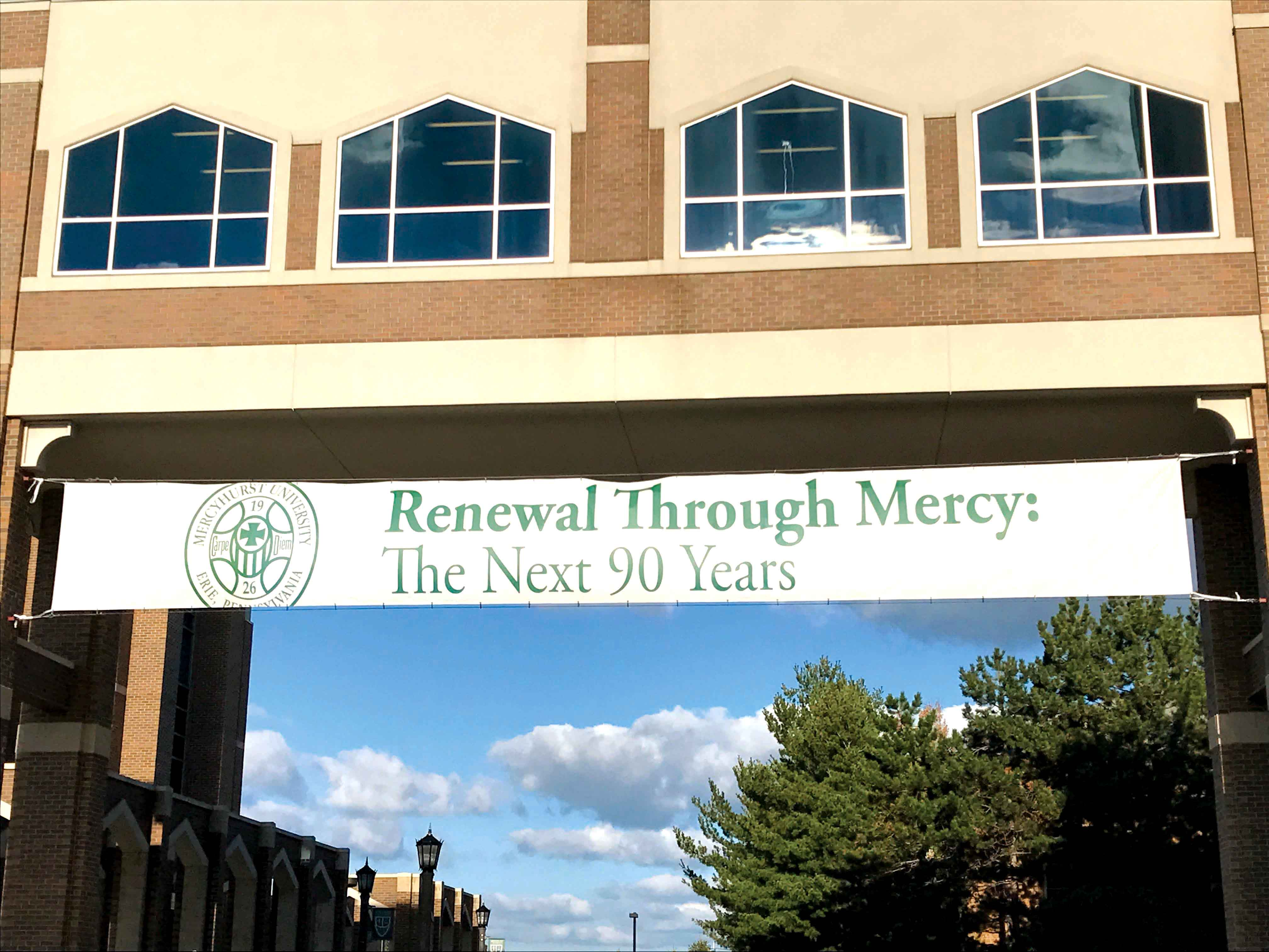 A sign hung from the Center for Academic Engagement's walkway at the front of campus, marking Mercyhurst's 90th year.