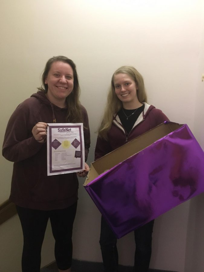 Kelly Peters and Emily Jarrett hold the boxes they placed around campus.
