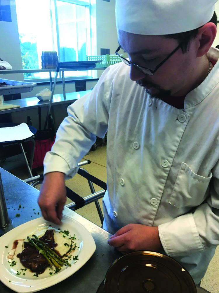 """Aaron Ellis, senior Hospitality Management major, opened the fall dining series with """"A Blackberry Dream,"""" making balsamic honey and mustard pork chops."""