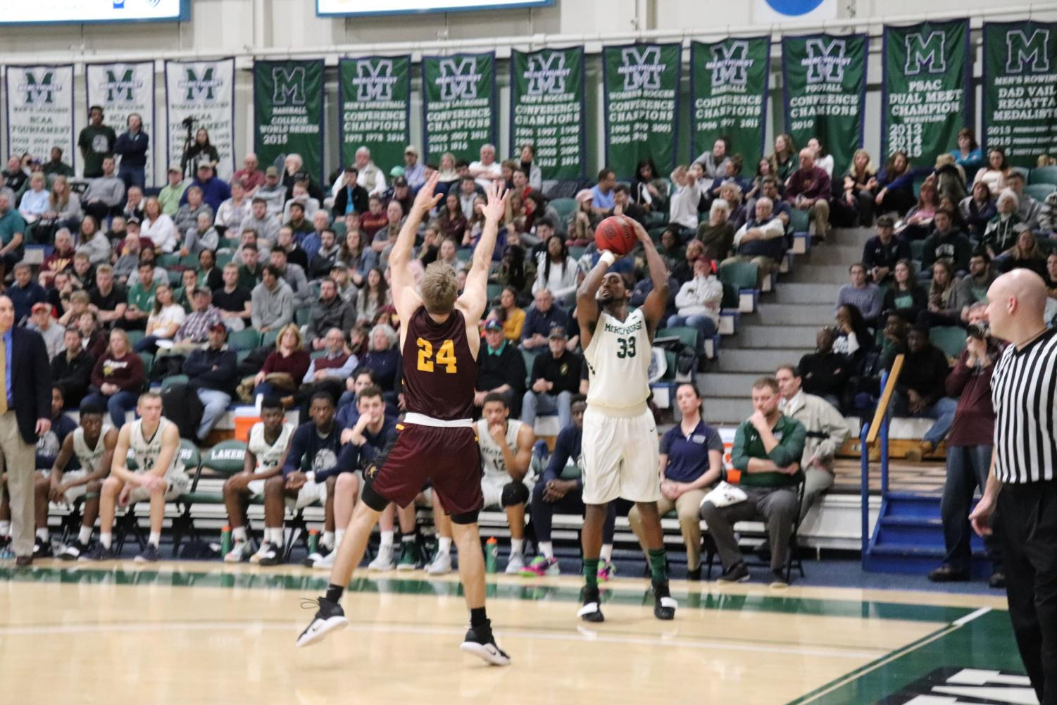 The Lakers' No. 33 Patrick Smith aims to shoot as Gannon University's Joe Fustine moves to block.  The Lakers were victorious with a 51-35 finish, taking home the 2019 Porreco Pride of Erie Cup.