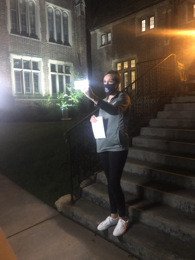 Lindsay Frank tells ghost stories on the steps of Egan Hall while livestreaming the event to alum via Zoom.