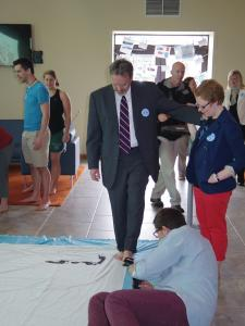 Zach Dorsch photo: Vice President for Student Life Gerard Tobin leaves his mark on the TOMS banner.