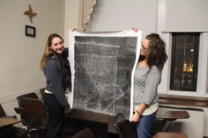 "Taylor Rollins photo: Public history majors Allie Stacy and KayAnn Warner hold a 1922 map of the Frontier Park area in the city of Erie for the ""Erie Places, Erie Stories"" project."