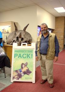 Nhi Tran photo: Greg Rasmussen, Ph.D., stands by a sign for his Protect the Pack Initiative after speaking with students and faculty about African Painted Dog Conservation on Friday, Feb. 6.