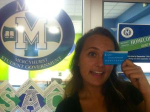 Salina Bowe photo: Mercyhurst Junior Helene Prince holds up the new MSG iCard in front of the MSG chambers. The iCard rewards students for participating in MSG events.