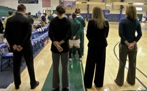Photo by Ethan Magoc: Mercyhurst College coach Deanna Richard (middle right) stands with her assistant coaches during the national anthem prior to her team's game against Clarion University on Wednesday, Jan. 19, 2011, at the Mercyhurst Athletic Center.