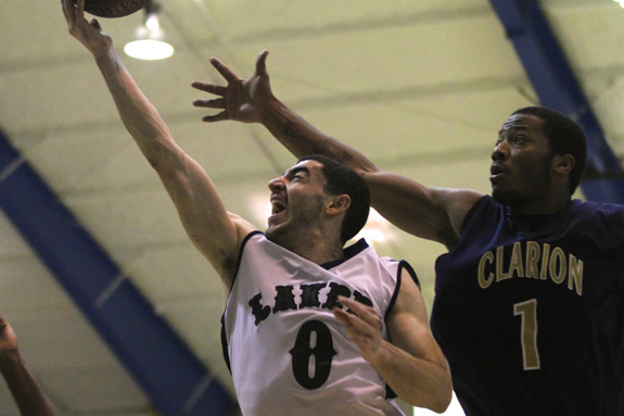Photo by Ethan Magoc: Mercyhurst College's Heiden Ratner scores a layup past Clarion University's Lloyd Harrison during the second half on Wednesday, Jan. 19, 2011, at the Mercyhurst Athletic Center.