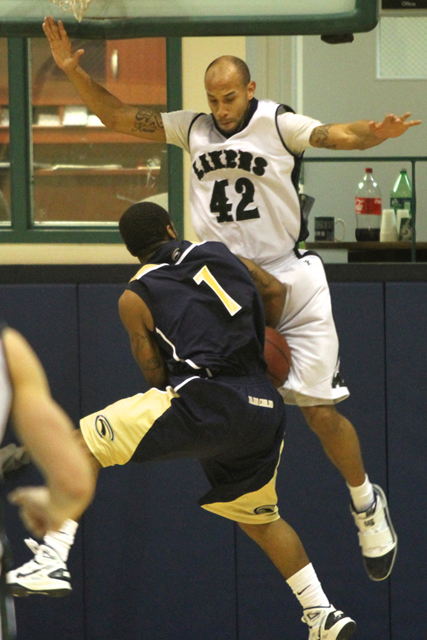 Photo by Ethan Magoc: Mercyhurst College's Bill Weaver (42) fouls Clarion University's Lloyd Harrison while trying to block his layup during the second half on Wednesday, Jan. 19, 2011, at the Mercyhurst Athletic Center.