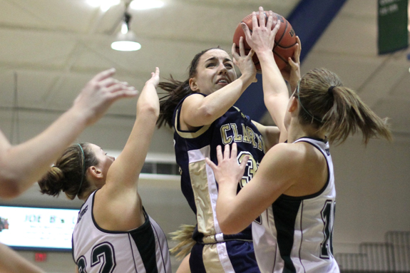 Photo by Ethan Magoc: Mercyhurst College seniors Samantha Loadman (right) and Amy Achesinski defend Clarion University's Mackenzie Clark during the first half on Wednesday, Jan. 19, 2011, at the Mercyhurst Athletic Center. Loadman registered a block on the play.