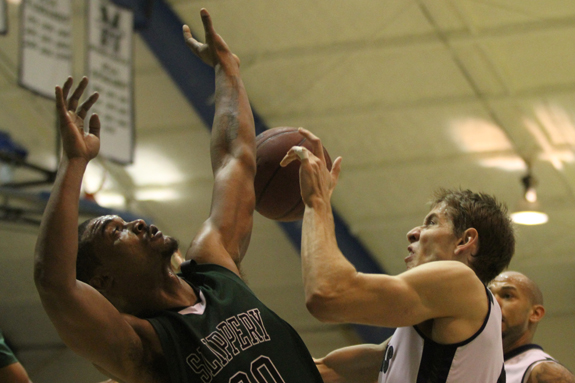 Ethan Magoc photo: Slippery Rock's Maron Brown, left, blocks a shot from Mercyhurst College's Iddo Cohen during the second half on Tuesday, March 1, 2011 at the Mercyhurst Athletic Center.