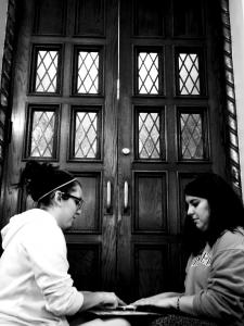 Staff photo: Cagle and Handerhan talk to the spirits, using a ouija board, outside the Mercyhurst Christ the King Chapel.