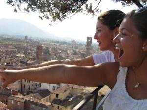 Guerra joined by a fellow traveler pointing towards the Guinigi Tower in Lucca, Italy