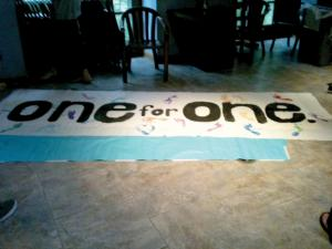 Alex Stacey, photo: A huge One for One banner was being signed with student's footprints at Wednesday's event.