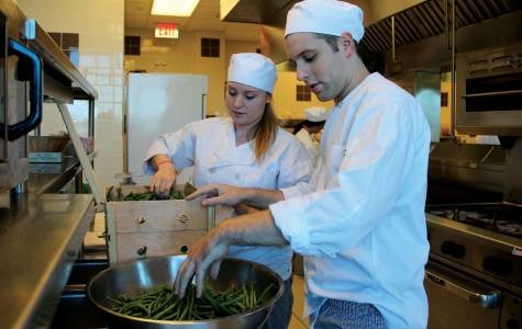 Senior Hospitality Management majors Katy Sieb and Aaron Crecraft develop their culinary skills.
