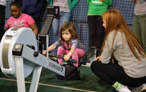 Freshman rower Amelia Kanonczyk guides a young girl using a rowing machine. The event offered activities in more than 10 sports.
