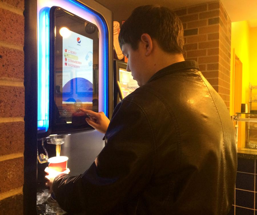 Student gets a beverage at the new pop machine in the Laker.