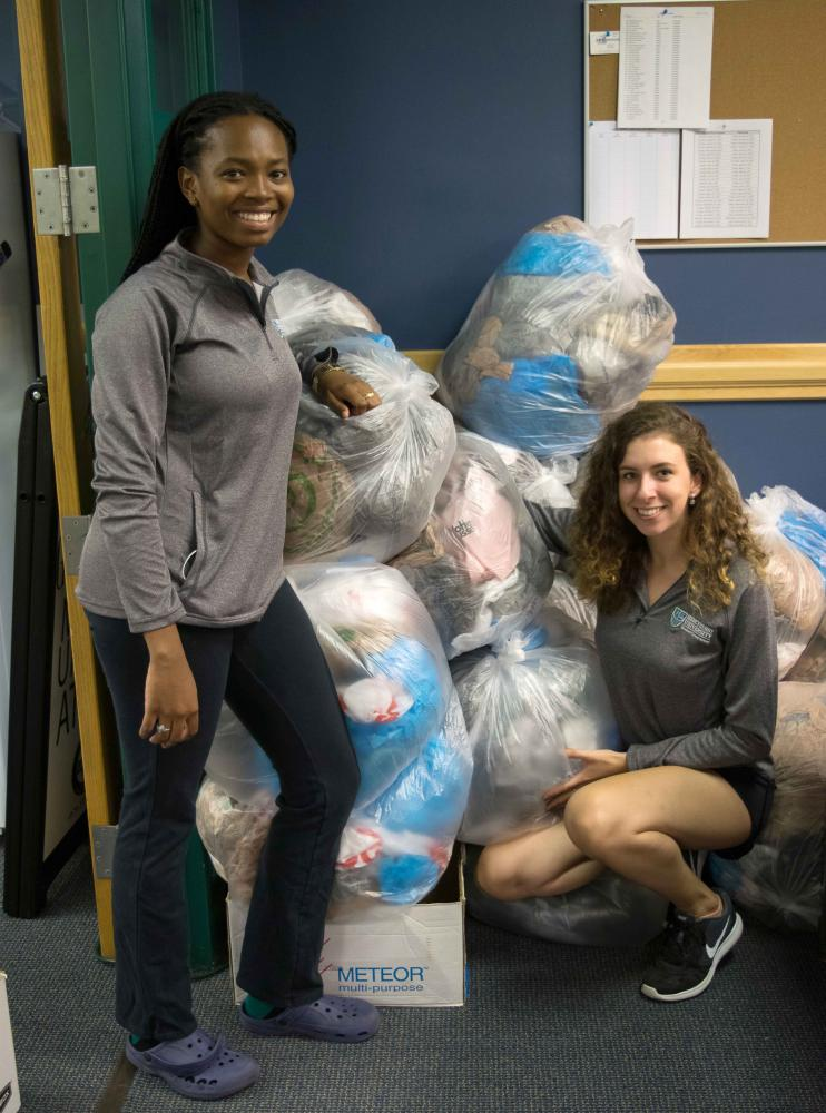 From left, Brittany Warren, Political Science major and MSG sophomore senator, and Rachel Lynch, junior Fashion Merchandising major, collect bags with the Mission and Sustainability Committee.