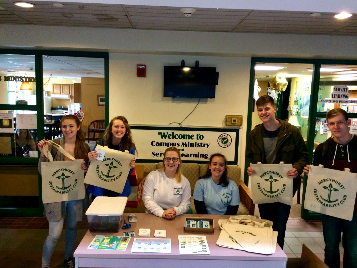 Sustainability Club members Emma Mader and Elly Buch, seated at center, help to hand out information and resources about recycling and composting in the Student Union. Freshmen Carly Holtzman, Julia Wrest, Nathan Brand and David Steets received free reusable tote bags for their involvement.