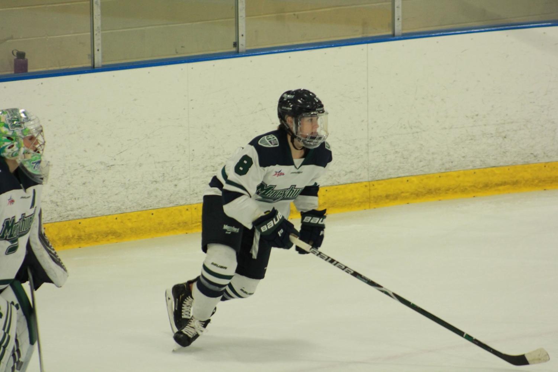 Mercyhurst defender Molly Blasen skates forward as goalie Sarah McDonnell looks on at left.