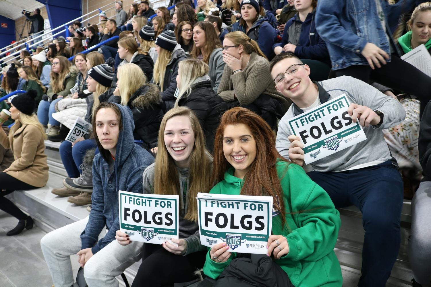 """Students show their """"I Fight For Folgs"""" signs at the men's hockey game on Saturday Jan. 26"""