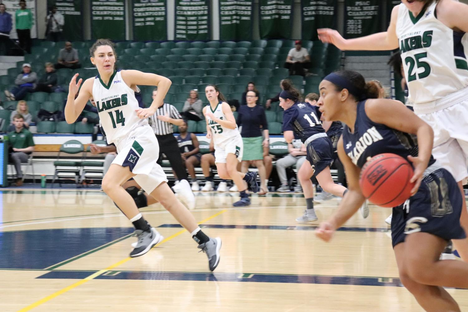 The Lakers' No. 14 Lauren Lapertosa races from the paint as a Clarion Golden Eagles player gets ready to dribble down court.
