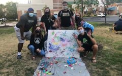"""Warde Hall RAs and residents mask up to enjoy an event called """"Pop the Bias"""" with splatter paint."""